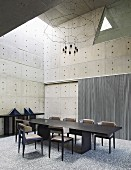 Geometric forms in dining room with concrete walls and dark furniture