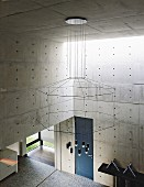 Impressive chandelier with geometric silhouette in architect-designed concrete house