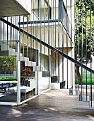 Floating metal staircase with straight balusters outside architect-designed house