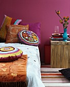 Indian summer in bedroom: bed decorated with colourful chenille and crocheted scatter cushions