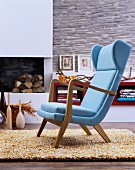 Pale blue easy chair on woollen rug in front of fireplace in living room