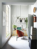 Designer shell chair at desk on trestles in small room with floor-to-ceiling lattice window