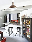 Black metal bar stools at counter with protruding stone worksurface next to cabinet with glass doors