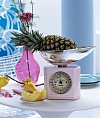 Pink retro kitchen scales and glass vase on round table