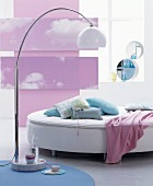 Round bed, standard lamps with marble base and pink photo mural of clouds on wall
