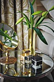 Vanity mirror, lily buds in gold vase and perfume bottles on round, mirrored bedside table