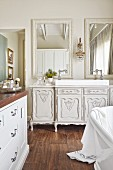 Antique white cabinet used as washstand with modern countertop basin below mirrors on bathroom wall