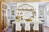 Bar stools with loose covers at island counter below kitchen utensils hung from pendant lamp in country-house kitchen