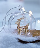 Festive bauble with glass reindeer inside amongst artificial snow