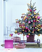 Christmas tree decorated with golden birds-of-paradise and baubles in deep pink, gold and silver