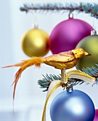 Gold bird-of-paradise Christmas tree decoration with feather tail