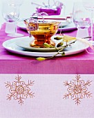 Table festively set with embroidered runner and silvered glass dishes in bright colours