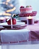 Tischgedeck weihnachtlich dekoriert mit rotem Apfel, Kerze und Dekoband