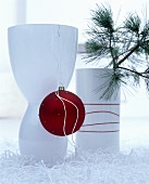 Elegant white vase decorated with red Christmas tree bauble