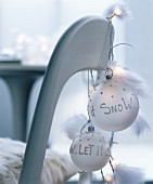 Chair with fur seat cover decorated with string of fairy lights and feathers and white baubles with festive mottoes