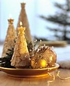 Weihnachtliche Deko mit goldenen Kugeln und Kerzen in Tannenbaumform auf Goldteller