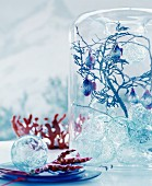 Fairy-tale Christmas arrangement of glass baubles, twigs and fish-shaped baubles in glass vase