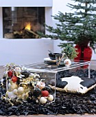 Plexiglas coffee table on black designer rug made from strips of leather in festively decorated interior with fireplace