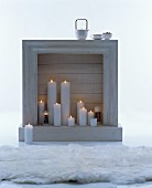 White fake fireplace festively decorated with lit white pillar candles