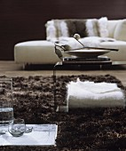 White and brown living room with modern chaise and side table on long-pile rug
