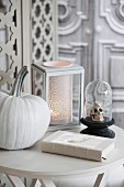 Halloween arrangement of white-painted pumpkin, skull ornament under glass cover and romantic candle lantern on table