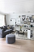 Scandinavian interior with white wood-clad walls, grey armchairs and pouffe next to set of coffee tables
