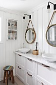 Washstand with twin, white countertop sinks and drawers in base cabinet below mirrors on white wooden wall