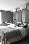 Elegant bed linen on double bed below canopies and panels of glossy fabric in luxurious bedroom in shades of grey