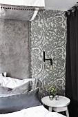 Bett und weisser Nachttisch vor tapezierter Wand mit Ornament Muster