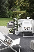 Wooden loungers with white seats on terrace with grey floor covering
