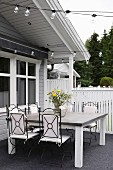Elegant metal chairs with white cushions around simple wooden table on terrace with grey floor adjoining wooden house