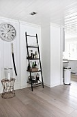Ladder shelves used as drinks cabinet next to candle lantern on side table below station clock in open-plan interior