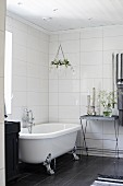 Tray table and free-standing bathtub in grey and white bathroom