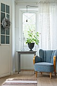 Blue 50s armchair next to geranium on table below window