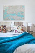 Double bed with blue blanket below map on wall and retro table lamp on bedside table