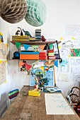 Wooden table below colourful boxes on bracket shelves and children's drawings on wall
