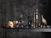 Various accessories and ornaments in charcoal-grey, Gothic ambiance (skull candlesticks, high-heels, bird figurines etc.)