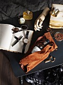 Model of hand, open notebook, bottle of wine wrapped in leather and Gothic jewellery on black table