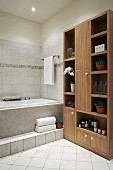 Potted plants on shelves in wooden cabinet in tiled bathroom