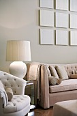 Grouping of pale, monochrome panels above sofa in pale beige living room