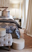 Elegant, grey bedlinen made from two-tone, plain chintz and hat box on bedroom bench in elegant bedroom