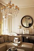 Kristallleuchter über Sofalandschaft, elegant dekorierter Konsolentisch mit klassischen Tischleuchten und runder Wandspiegel