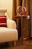Branch of red leaves in spherical vase on elegant side table, floor-length curtains and armchair with red and white scatter cushion
