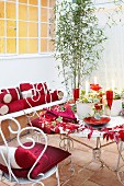 Bistro table and white, vintage metal chairs in tiled courtyard with red accessories