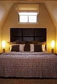 Bed with scatter cushions against dark brown leather headboard flanked by artistic lamps in attic bedroom