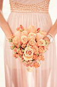 Romantic bouquet of roses held in hands in front of wedding dress