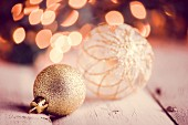Lighting effects and gold baubles on rustic wooden surface