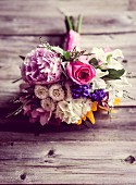 Garden bouquet of peonies, phlox and roses on rustic wooden surface