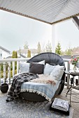 Cushions, fur rug and blankets on lounge chair on roofed terrace