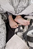 Man's bare feet amongst a tangle of bed linens